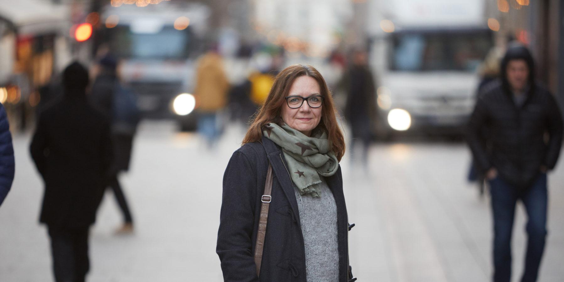 En kvinne står alene på gata.