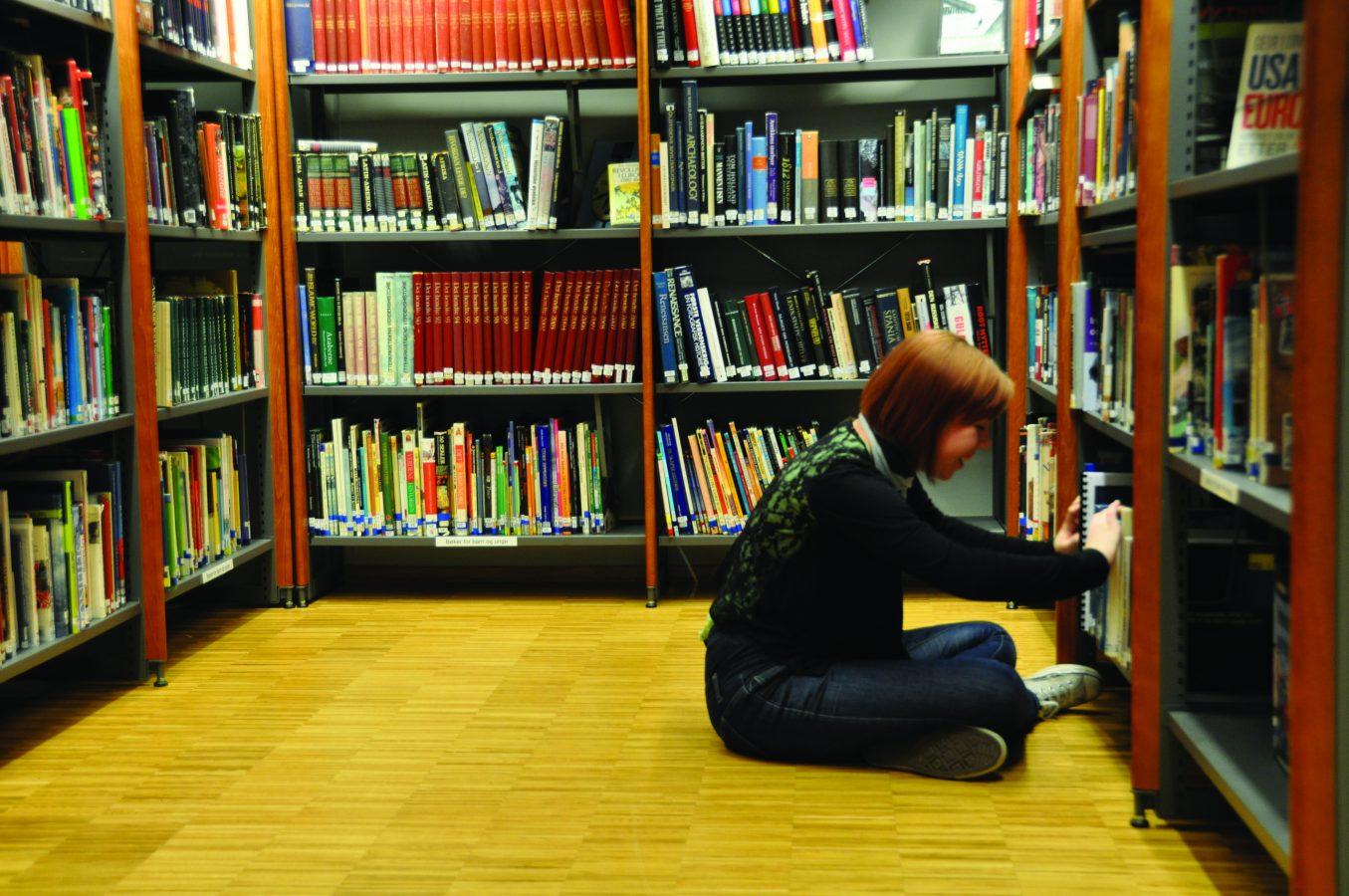 Jente setter på gulvet i et bibliotek og blar i bøker