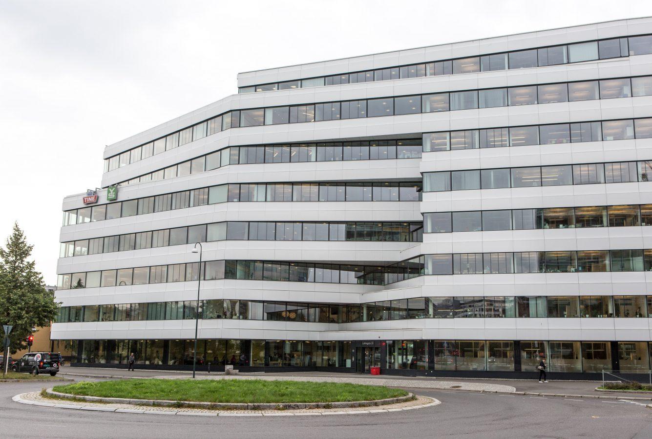 Bilde av en stor, hvit bygning med mange vinduer. På huset henger to skilt, hvor det står Tine og YS.