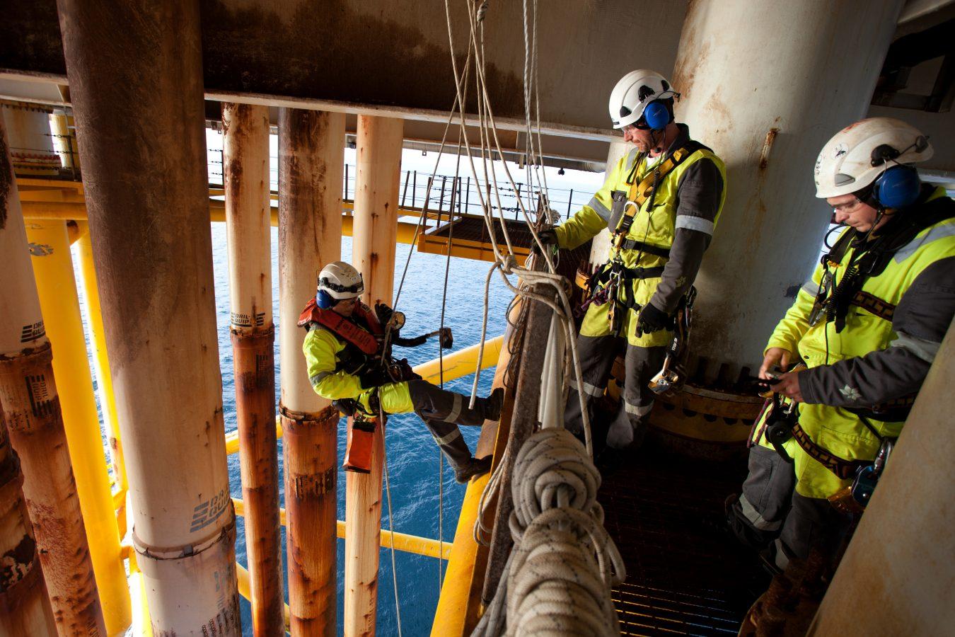 Tre klatrere i arbeid på en plattform i Nordsjøen. En er i ferd med å fire seg ned langs konduktorene for å inspisere en reparert skade.  Foto: Roger Hardy/Samfoto
