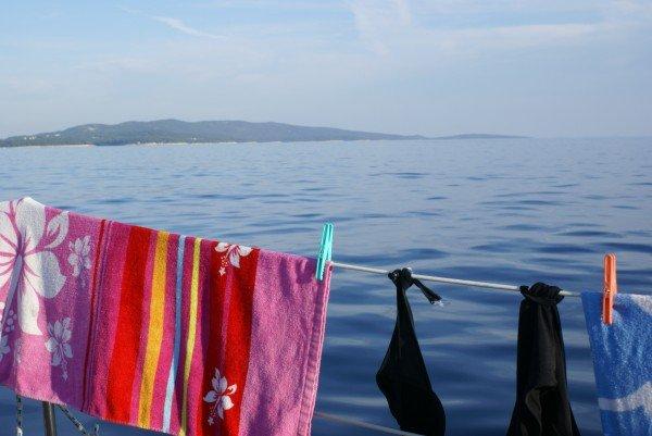 Håndklær og badetøy henger til tørk på rekka av en seilbåt. I bakgrunnen ses blått hav og himmel. Foto: Liv Hilde Hansen