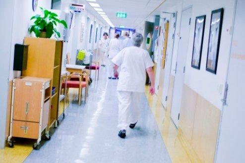 En pleier i hvite klær haster ned en korridor på et sykehus. Foto: Delta
