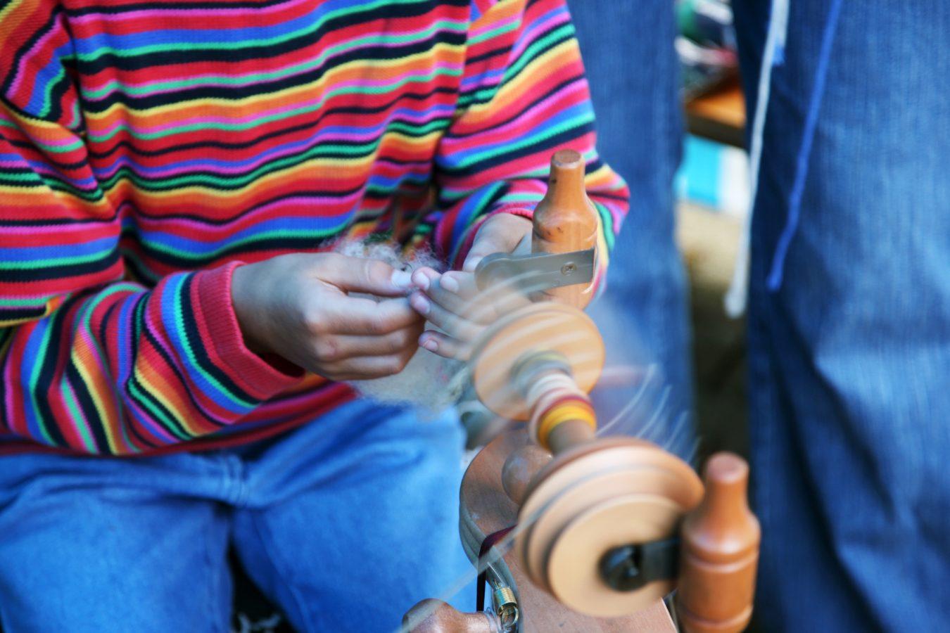 Et barn på jobb spinner garn. Bevegelsesuskarphet på rokk. Foto: Istock