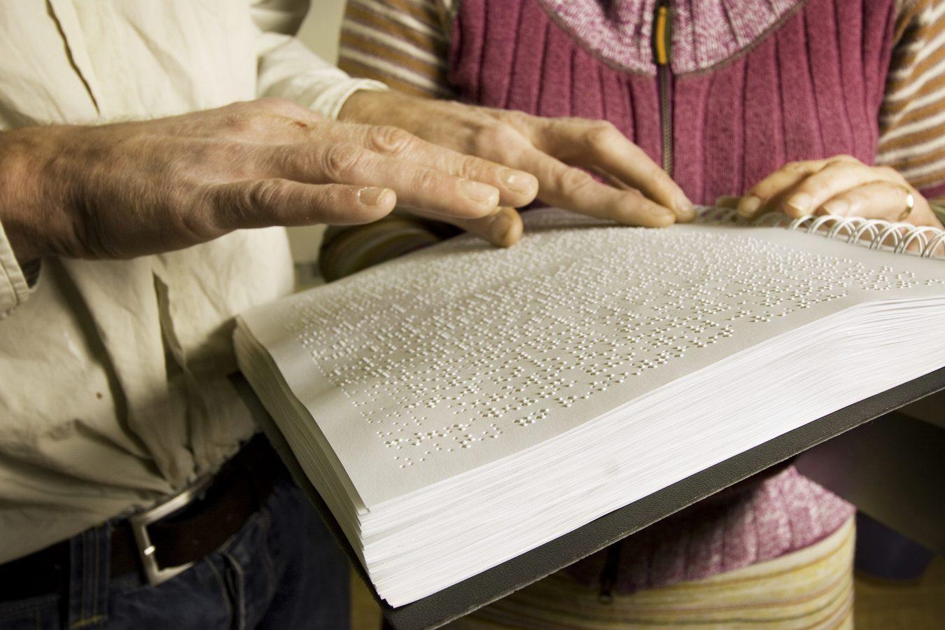 Blind i arbeidslivet. Mann leser rapport sammen med sin kvinnelige sjef. Blindeskrift. Foto: Steffen Rikenberg/Scanpix