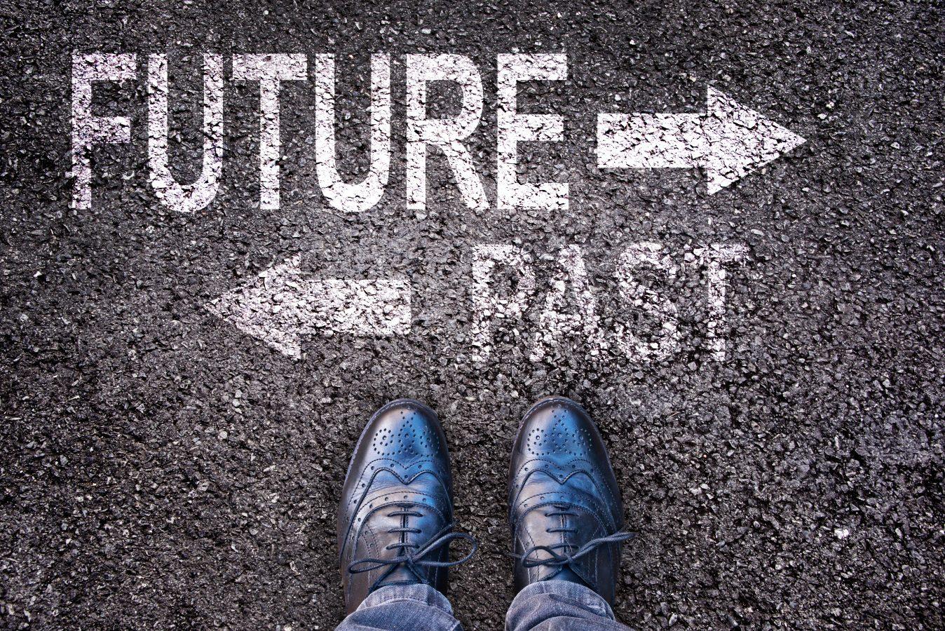 Føtter og ord fremtid og fortid malt på en asfaltert vei. Foto: Istock