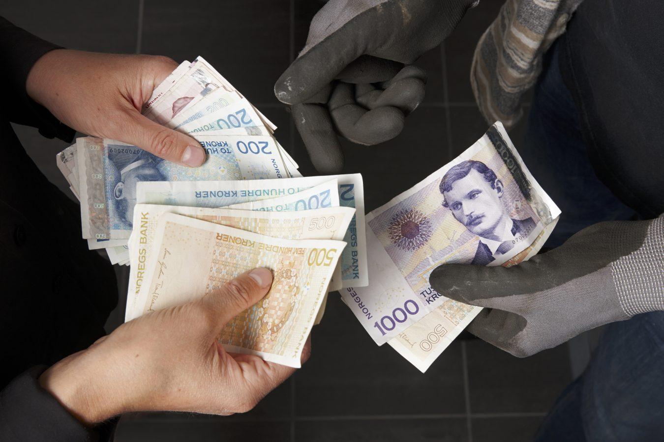 Kvinne betaler kontant til håndverker; svart arbeid; kontanter, cash, betaling, lønn, penger.  Foto: © Kerstin Mertens / Samfoto