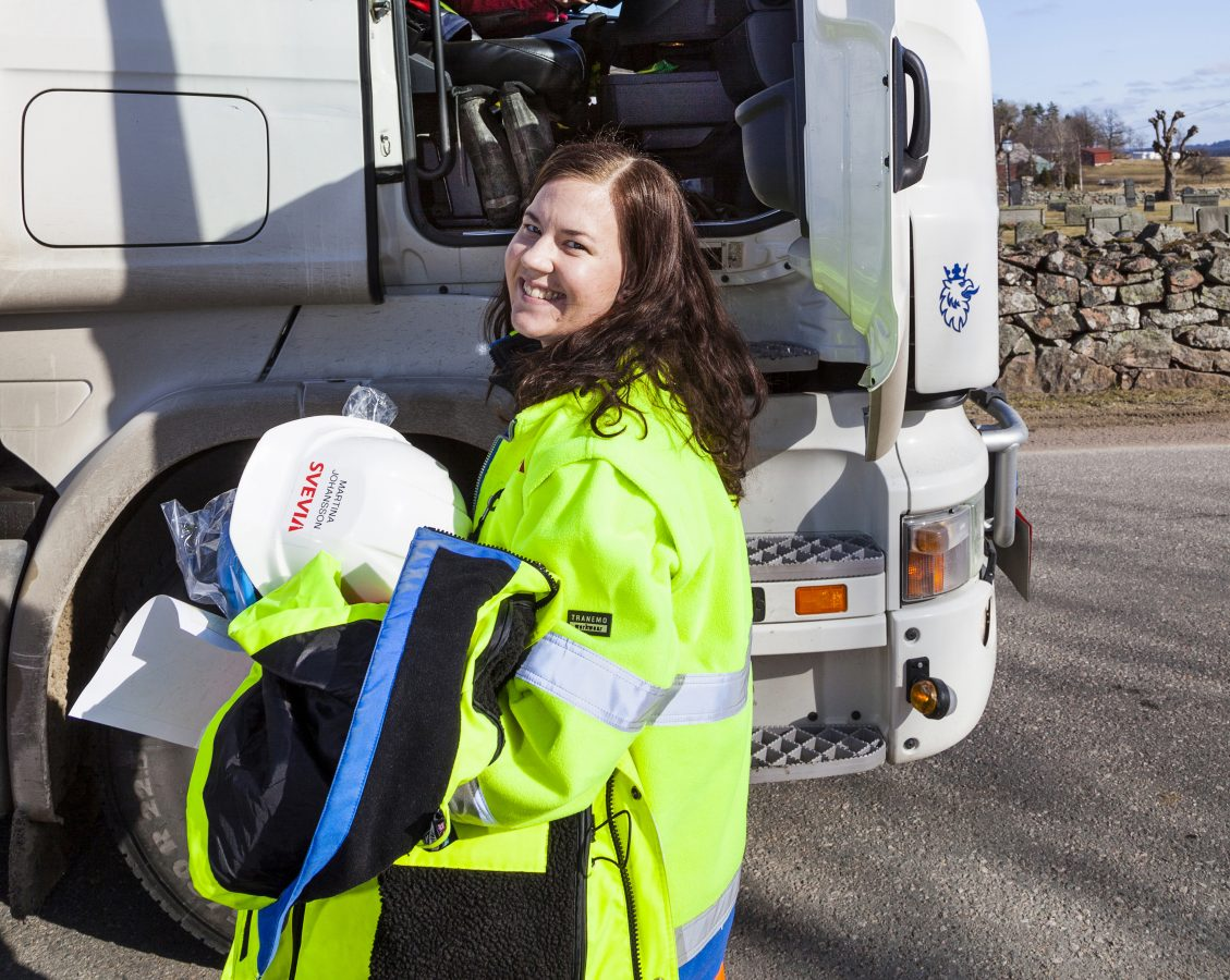 Ung jente i gult arbeidstøy står utenfor en lastebil.
