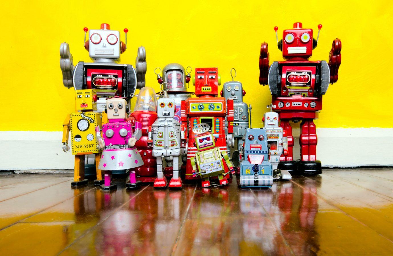 Retro robot leke på et treguld, med gul vegg bak.
