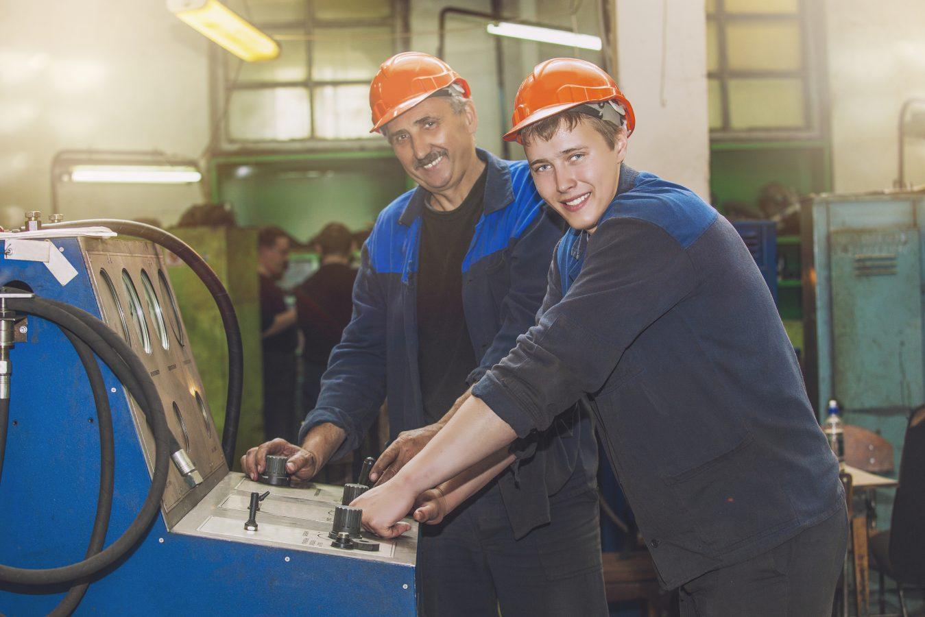 En lærling og en instruktør står ved en maskin. De har på orange hjelmer og blått arbeidstøy.