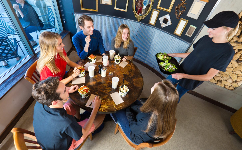 Ungdommer sitter på cafe og blir servert av en annen ungdom som er i sin første sommerjobb.