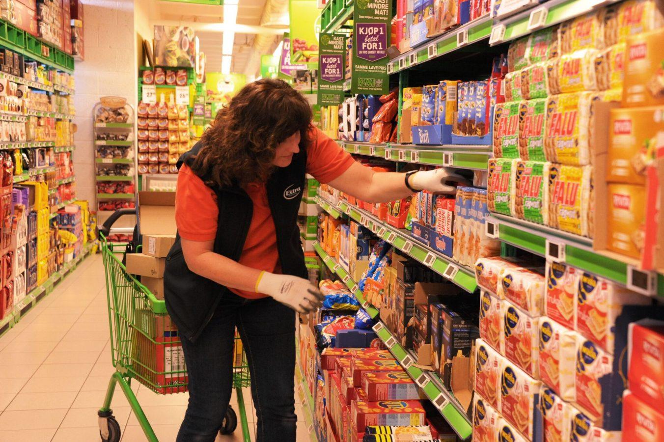 En kvinnelig butikkansatt stabler varer inn i hyllene i en matvarebutikk.