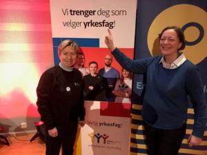 F.v.: Elisabeth Lange, sekretariatsleder i WorldSkills Norway og Bente Søgaard, seniorrådgiver i YS, peker på et skilt der det står «Vi trenger deg som velger yrkesfag»