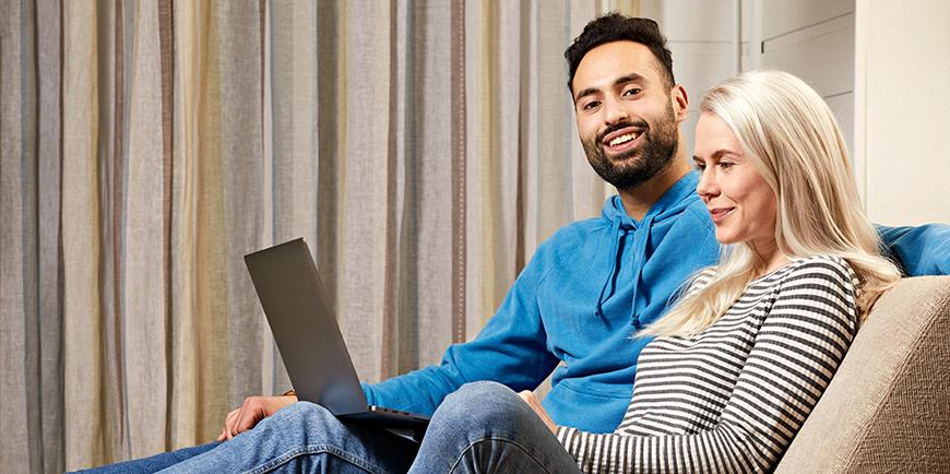 Et ungt par sitter i en spfa og ser på en PC sammen.