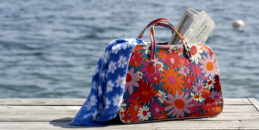 Veske på brygge, med røde og rosa blomster. Avis stikker opp. Blått håndkle stikker ut.