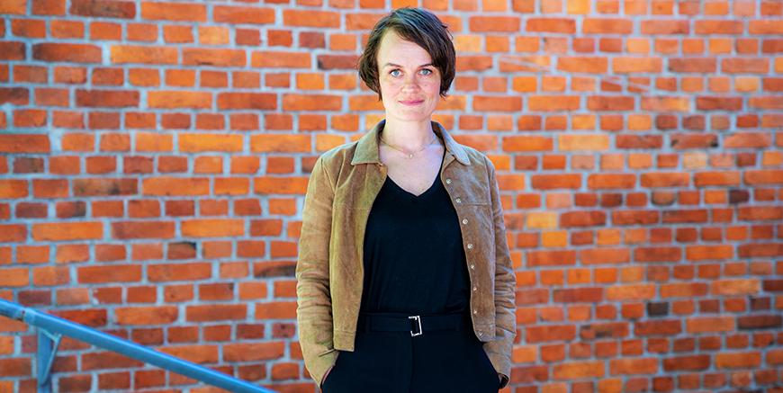 Nina Falck er sjeføkonomi YS. Her er hun avbildet mot rød murvegg.