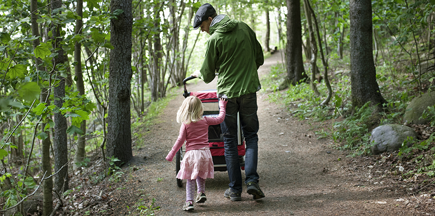 Far og datter på trilletur i skogen.  NB! Modellklarert.