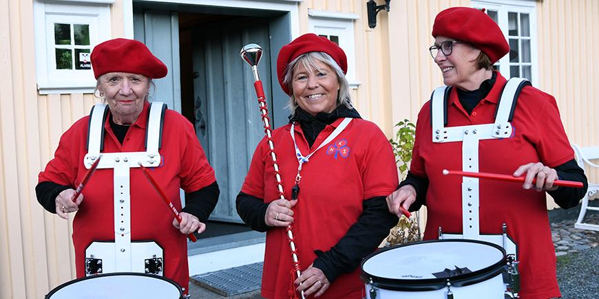 Tre damer står med trommer og i røde skjorter og alpeluer.