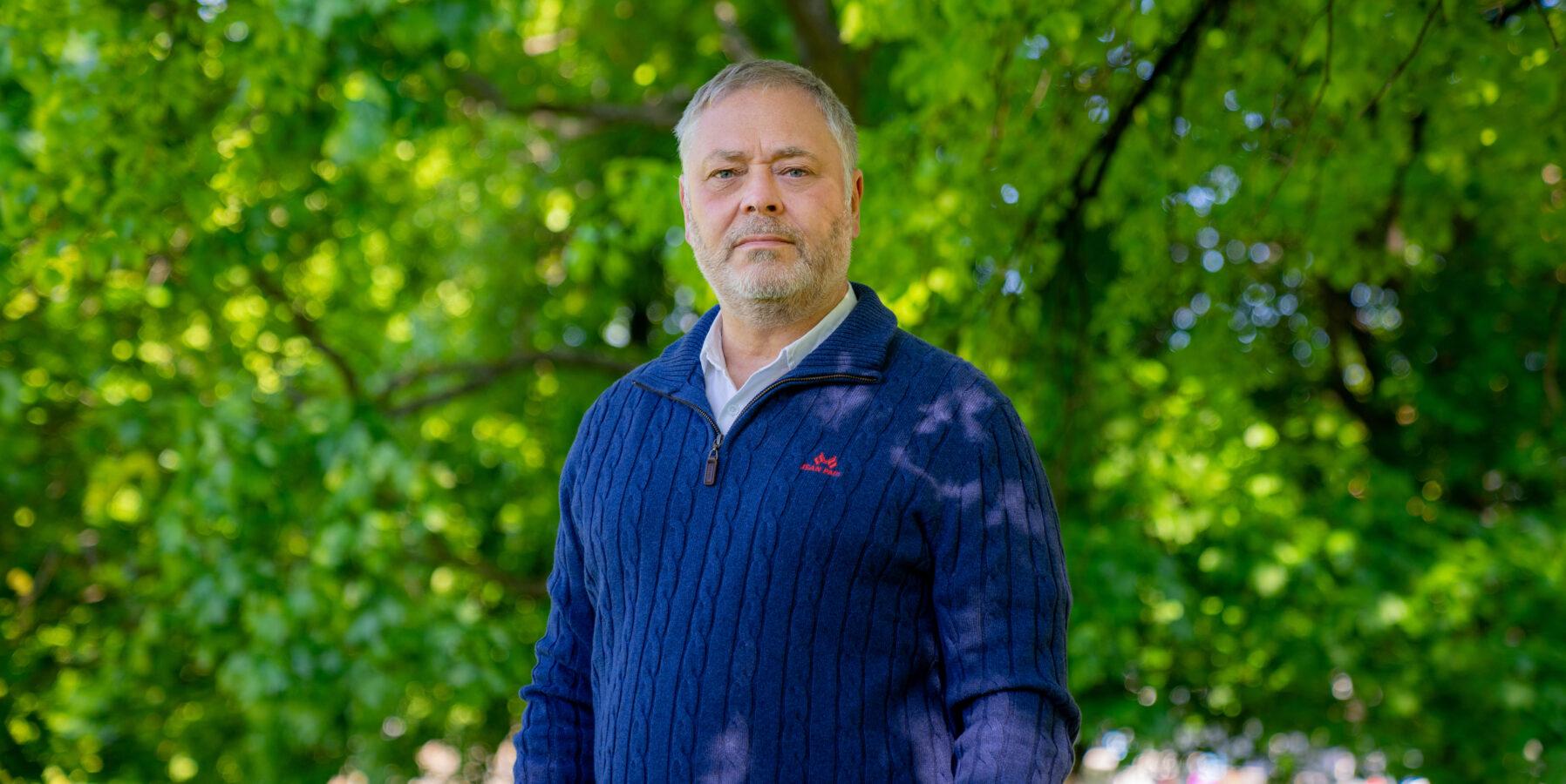 YS-leder Erik KOllerud i blå genser mot grønne trær i bakgrunnen.